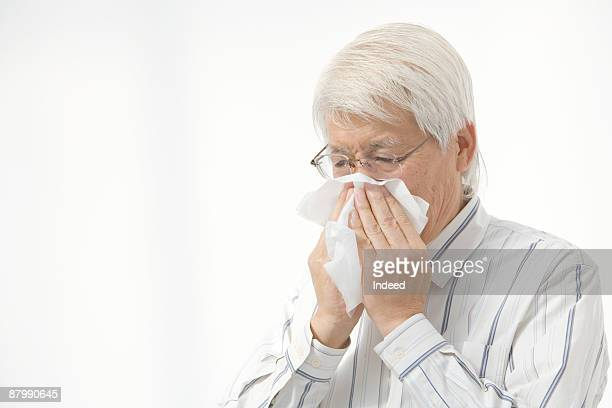 Senior man blowing his nose
