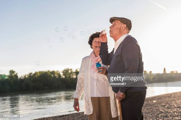 Senior man blowing soap bubbles on the beach at sunset