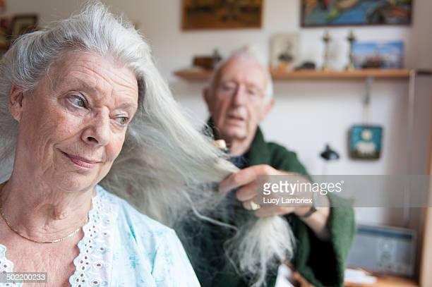 Senior man brushing his wife's long grey hair