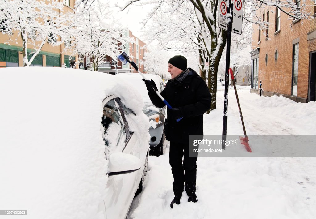 Senior man brushing snow from car on city street. : Stock Photo