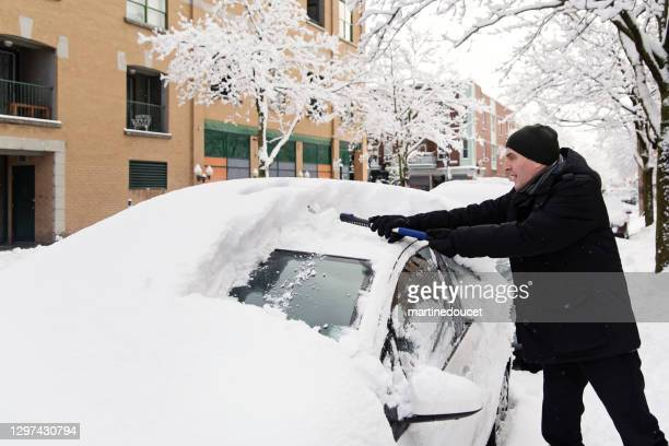 "senior man brushing snow from car on city street. - ""martine doucet"" or martinedoucet stock pictures, royalty-free photos & images"