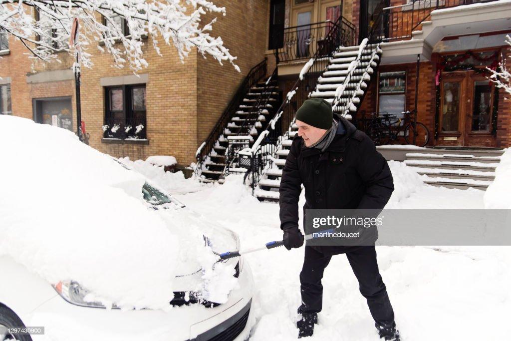 Senior man brushing snow from car on city street. : Stock Photo