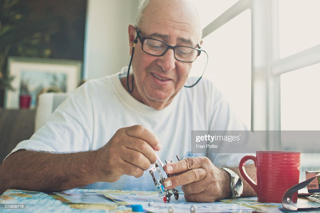 Senior man building a robot. : Stock Photo