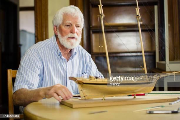 Senior man building handmade model sailboat in his store