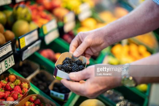 senior man buying fruits in grocery store - produce aisle stock pictures, royalty-free photos & images