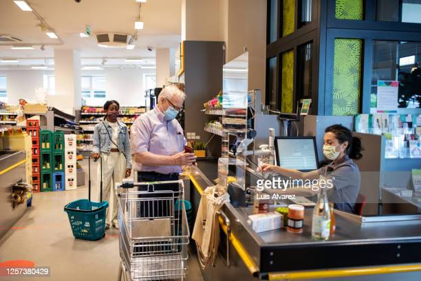 senior man buying groceries in supermarket - prophylaxie photos et images de collection