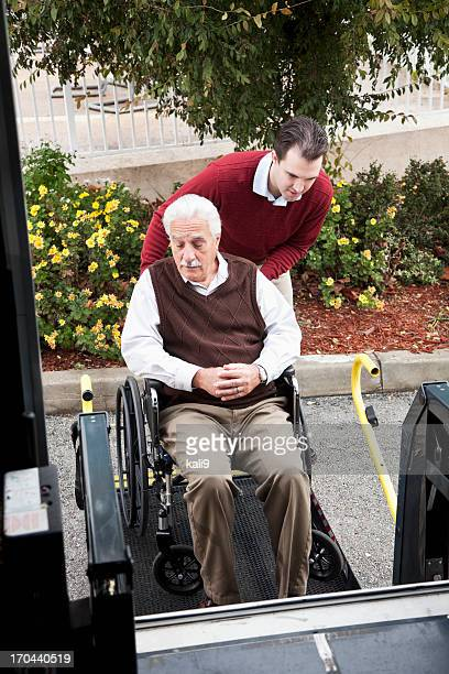 Senior man by minibus with wheelchair lift