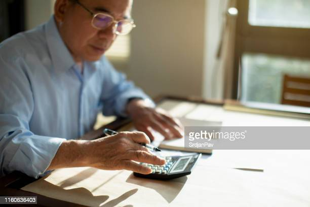 senior man calculating finances - pension stock pictures, royalty-free photos & images