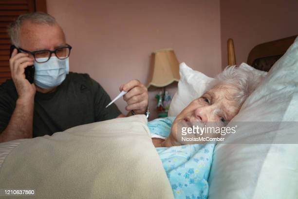senior man calling a helpline while his partner is sick - symptom stock pictures, royalty-free photos & images