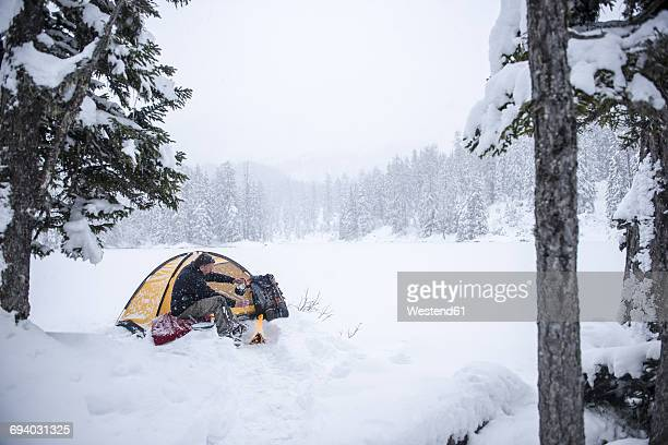 Senior man camping in snow-covered landscape