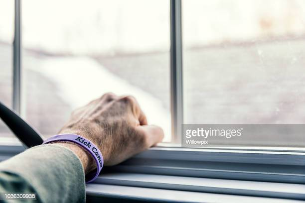 senior man cancer patient clenched fist wristband hand - survival stock pictures, royalty-free photos & images