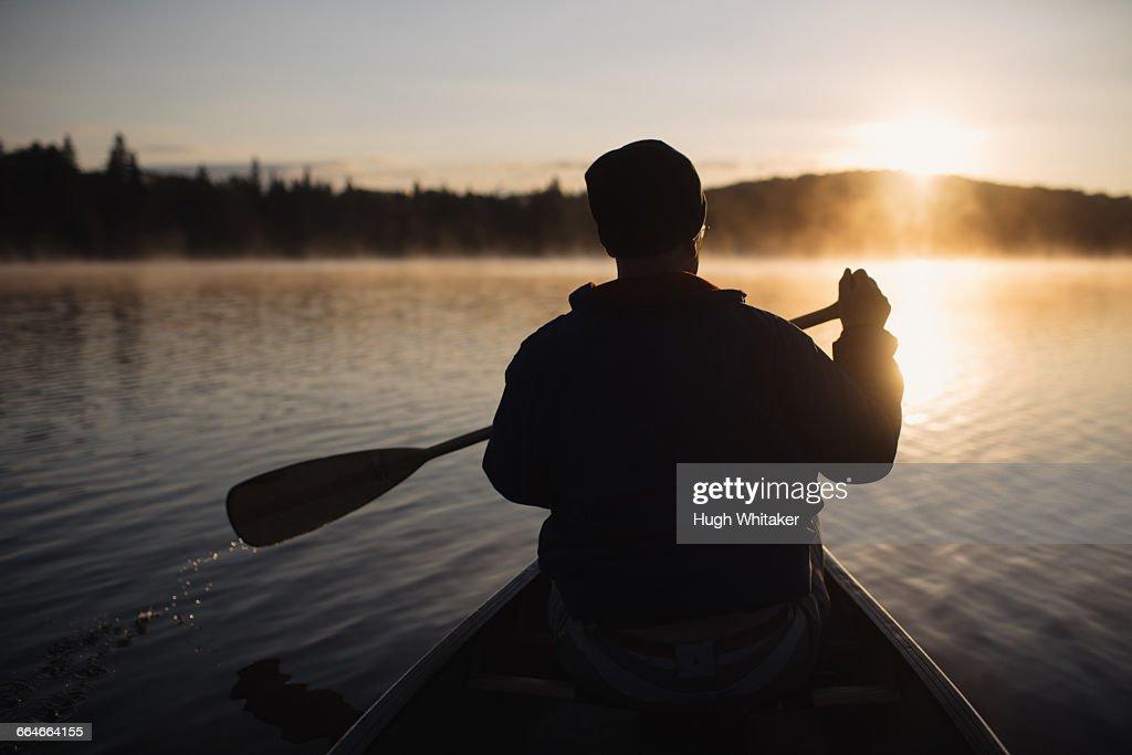 Senior man canoeing on lake at sunset, rear view : Stock Photo