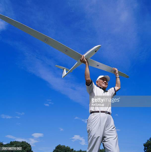 Senior man carrying model plane, low angle view