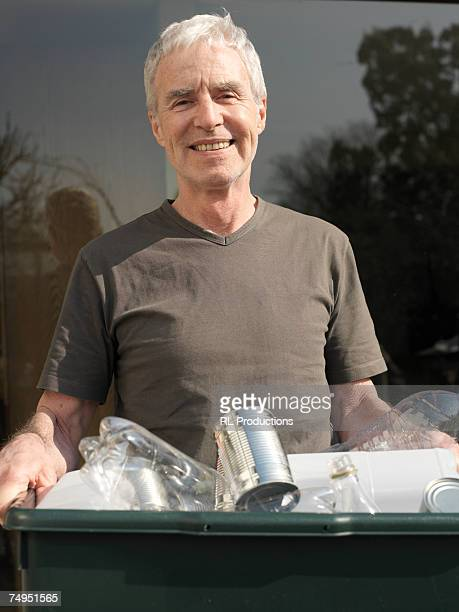 Senior man carrying recycling crate, smiling, portrait