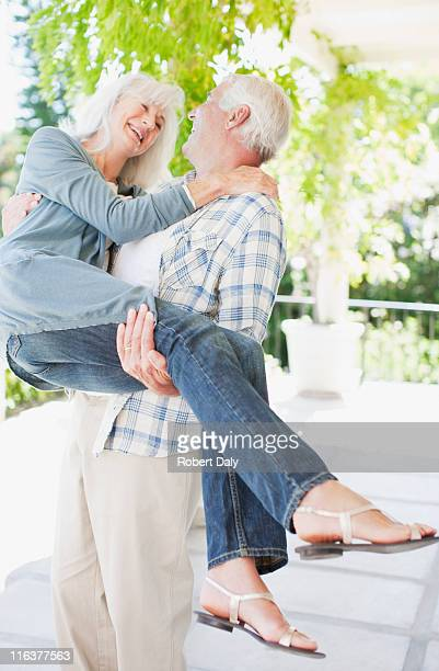 Senior man carrying wife on patio