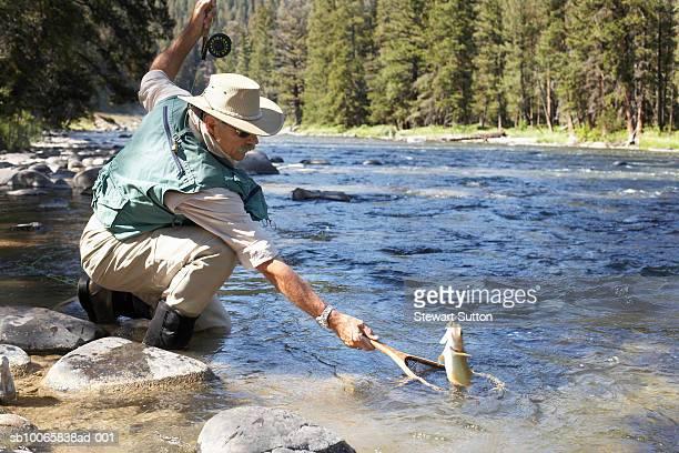 Senior man catching fish in river