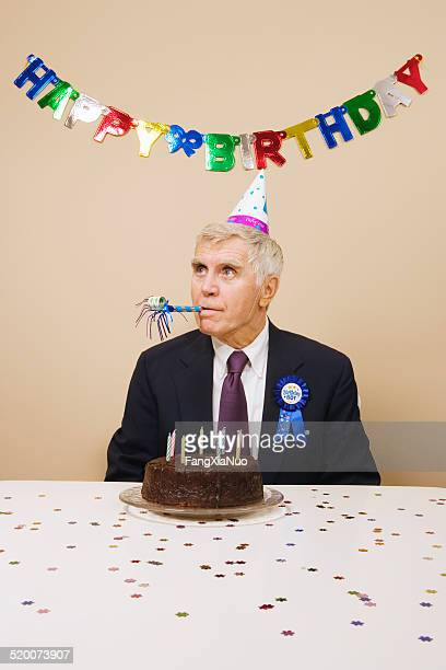 senior man celebrating birthday, indoors - party blower stock pictures, royalty-free photos & images