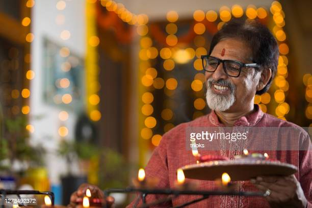 senior man celebrating on occasion of diwali festival - hinduism stock pictures, royalty-free photos & images