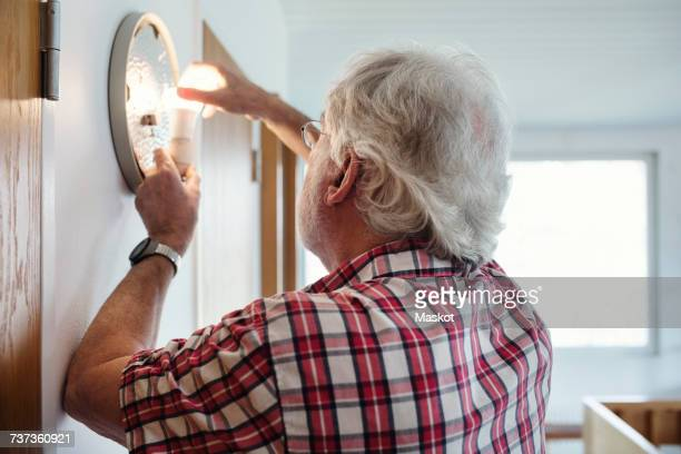 Senior man changing light bulb in sconce at home