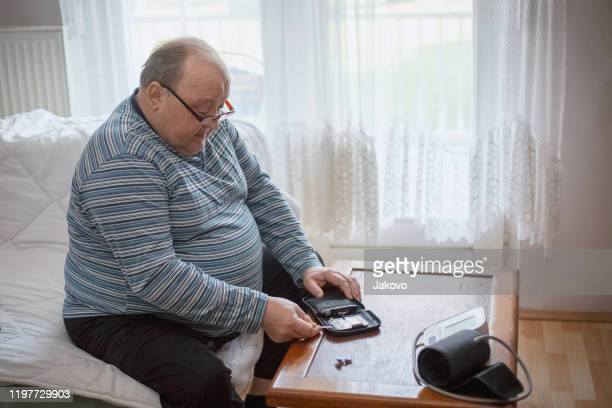 senior man checking blood sugar levels - heavy stock pictures, royalty-free photos & images