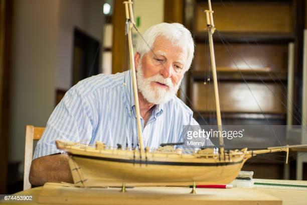 Senior man checking handmade wooden sailboat model