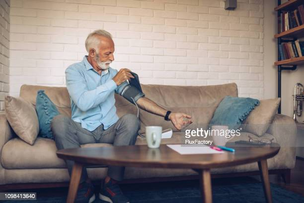 senior man checking his blood pressure - heart attack stock pictures, royalty-free photos & images