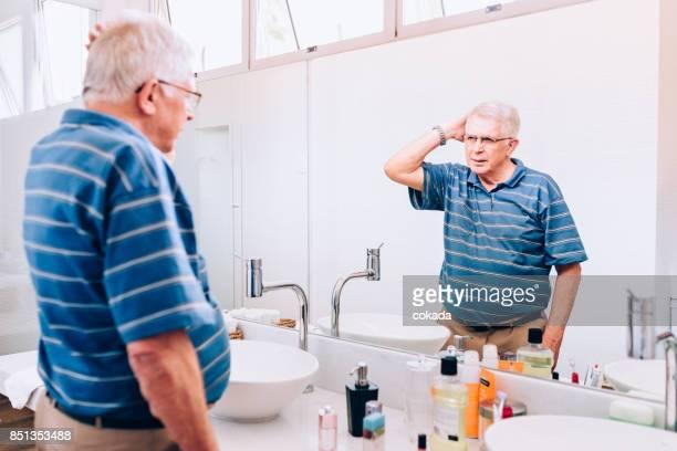 Senior woman Überprüfung sein Haar