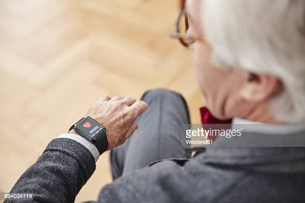 Senior man checking medical data on smartwatch