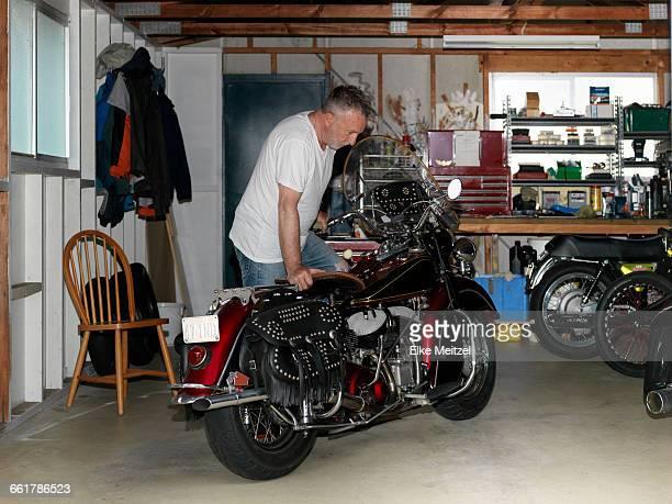 Senior man checking over motorcycle in garage