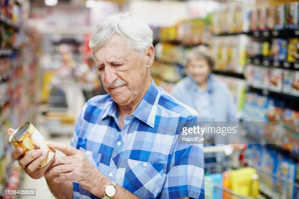 senior man checking product label in supermarket as wife watches - canned food stock pictures, royalty-free photos & images