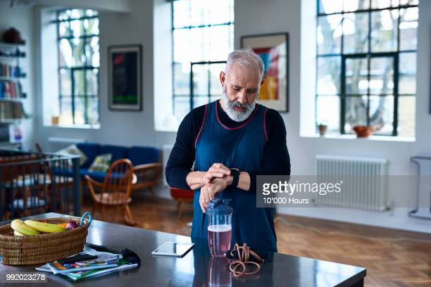 senior man checking smart watch before exercising - wearable computer stock pictures, royalty-free photos & images