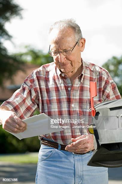 a senior man checking the mailbox - domestic mailbox stock pictures, royalty-free photos & images