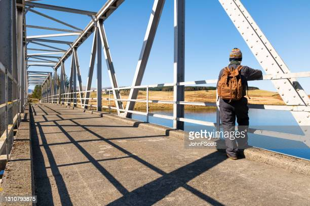 senior man checking the view from a bridge - johnfscott stock pictures, royalty-free photos & images