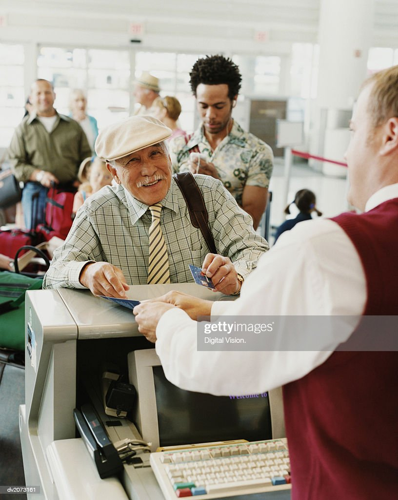 Senior Man Checks Into an Airport : Stock Photo