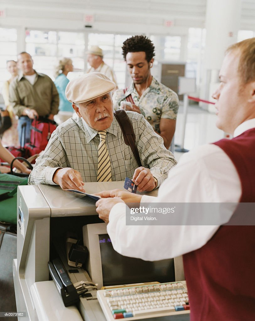 Senior Man Checks Into an Airport With a Credit Card : Stock Photo