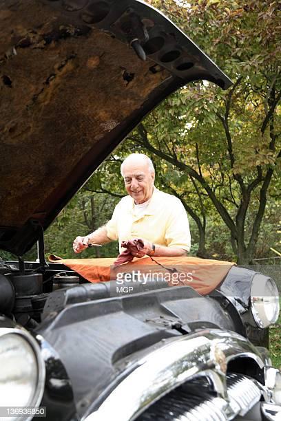 Senior man checks oil