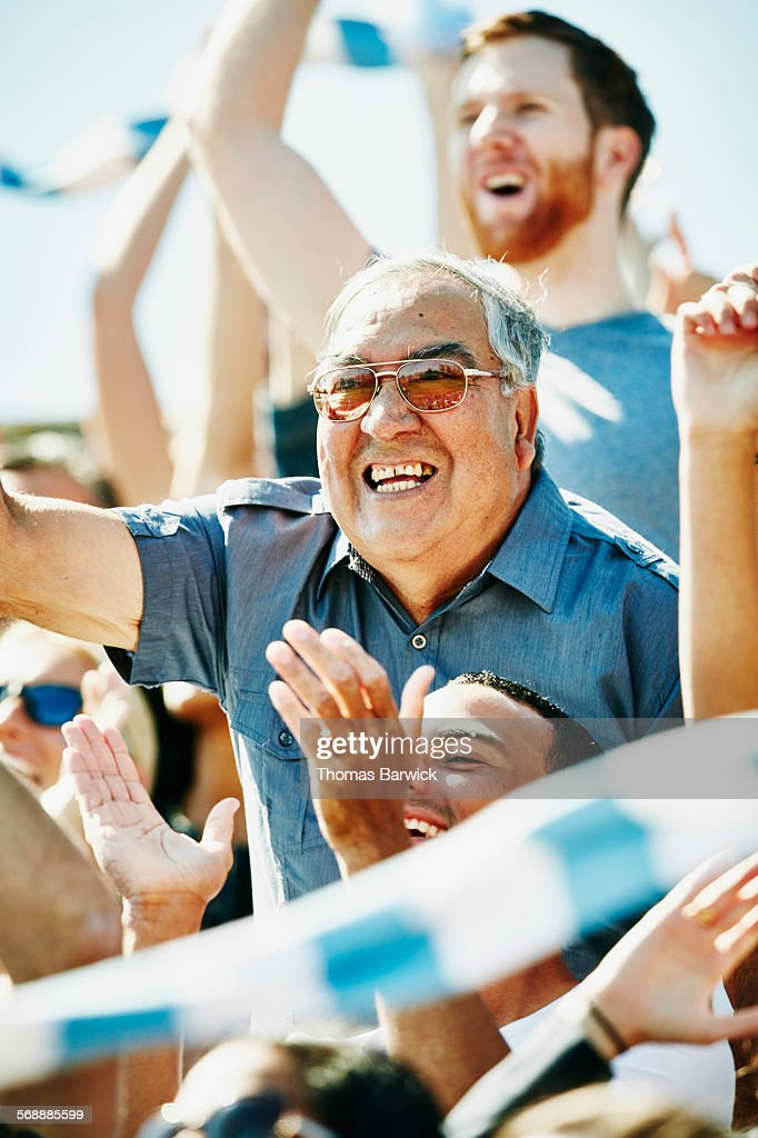 Senior man cheering in crowd during soccer match : Stock Photo