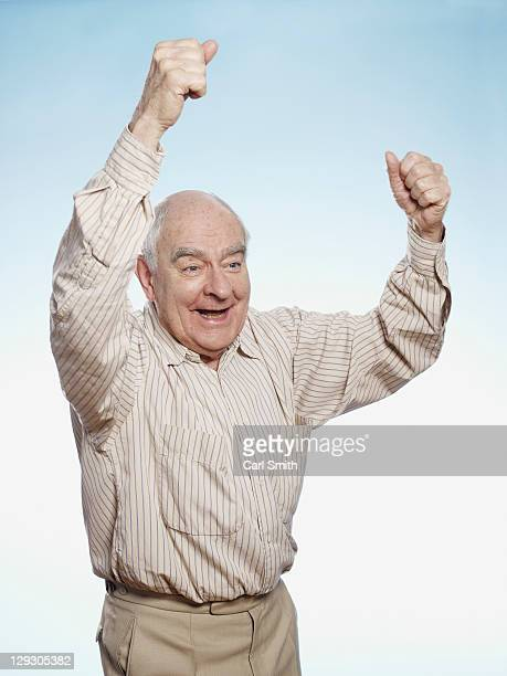 senior man cheering - beige pants stock photos and pictures