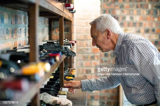 senior man choosing wine bottle from rack at home - collection stock pictures, royalty-free photos & images