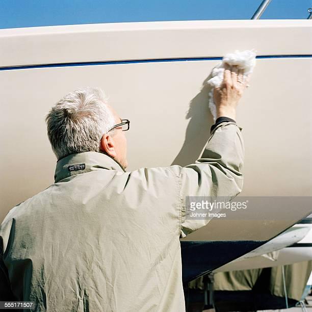 senior man cleaning boat - västra götalands län stockfoto's en -beelden