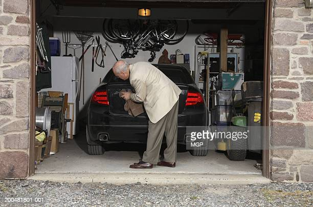 Senior man cleaning car in garage, rear view