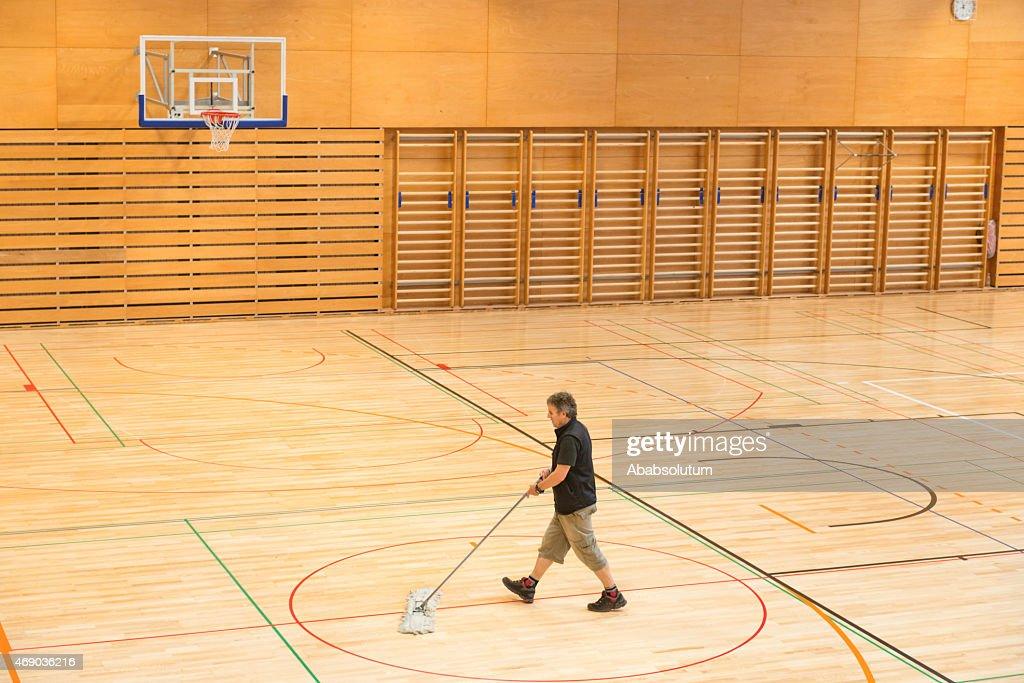 Senior Man Cleaning Floor in School Gymnasium, Europe : Stock Photo