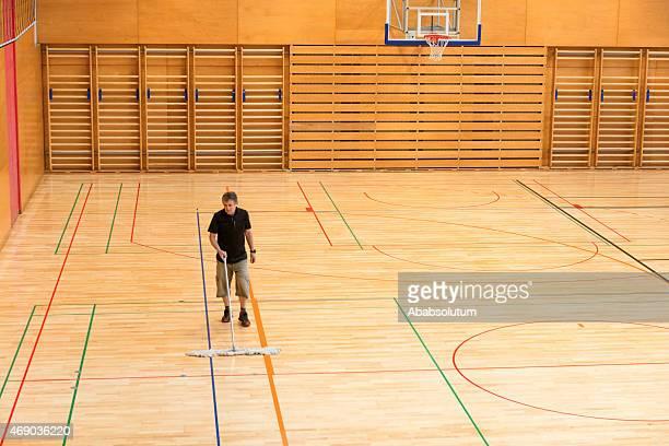 Senior Man Cleaning Floor in School Gymnasium, Europe