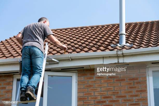 senior man cleaning gutters - repairing stock pictures, royalty-free photos & images