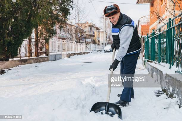 senior man cleaning snow - digging stock pictures, royalty-free photos & images