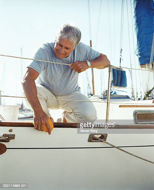 Senior man cleaning yacht, smiling