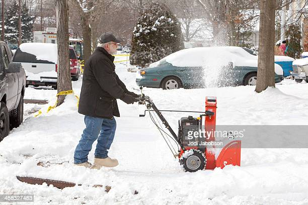 Senior man clearing snow with a snowblower  RM