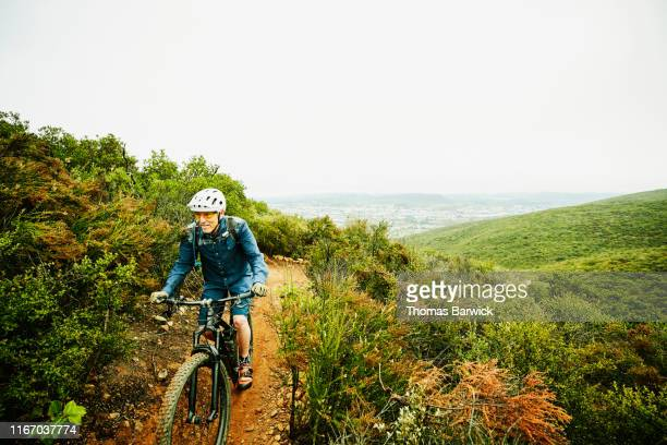 Senior man climbing hill while riding mountain bike on trail