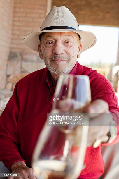 Senior man clinking wine glass
