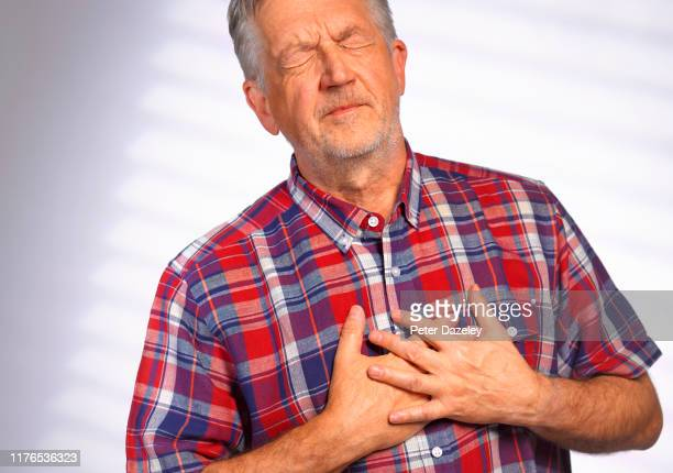 senior man clutching heart in pain - terrified stock pictures, royalty-free photos & images